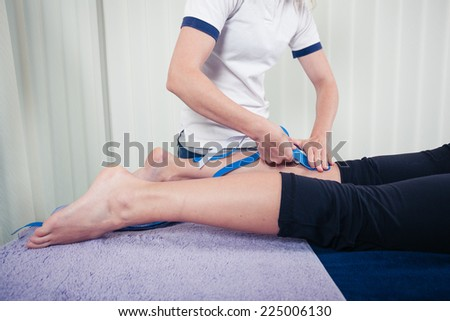A physiotherapist is applying kinesio tape to a patient's leg - stock photo