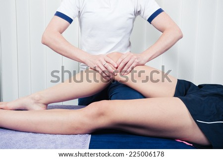 A physiotherapist is treating a patient's knee - stock photo
