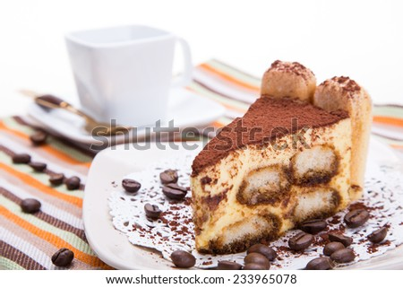 A pice of tiramisu cake on a white dish. - stock photo