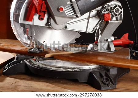 A pice of wood in a mitre saw - stock photo