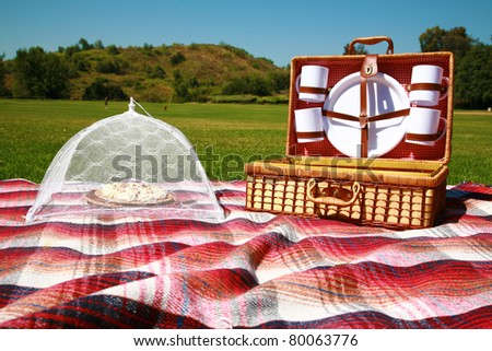 a picnic basket with all the fixins in a park outside one spring day, with banana cream pie for desert - stock photo