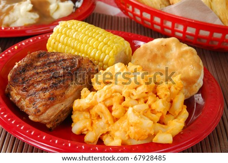 A picnic table set with golden fried chicken - stock photo