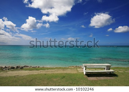 a picnic table situated along a coast road overlooking the Caribbean Sea in Barbados - stock photo