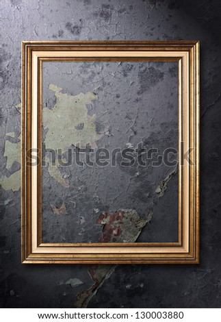 A picture frame sits empty on a cracked and grungy wall. - stock photo