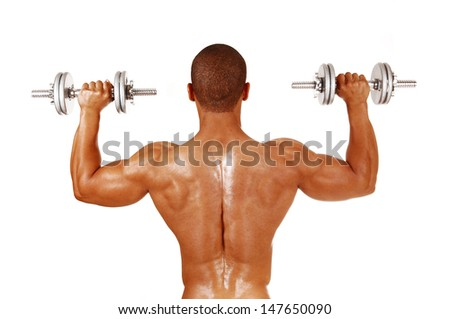 A picture from the back of a young bodybuilder, lifting two silver color dumbbells in his exercises.  - stock photo