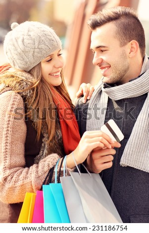 A picture of a beautiful couple shopping with a credit card in the city - stock photo