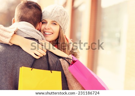 A picture of a beautiful woman hugging a man while shopping - stock photo