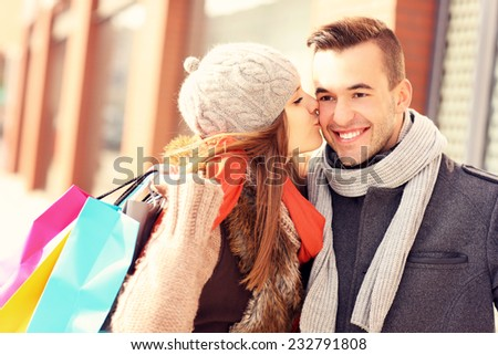 A picture of a beautiful woman kissing a man while shopping - stock photo