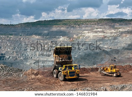 A picture of a big yellow mining truck and bulldozer at work site - stock photo