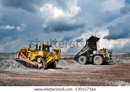 A picture of a big yellow mining truck and bulldozer at worksite
