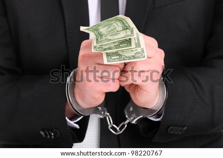 A picture of a businessman in handcuffs holding dollars