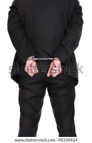 A picture of a businessman in handcuffs standing over white background