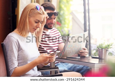 A picture of a couple of tourists resting in a cafe