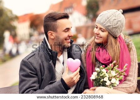 A picture of a couple on Valentine's Day in the park with flowers and heart - stock photo