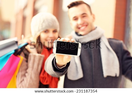 A picture of a couple showing smartphone while shopping - stock photo