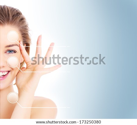 A picture of a female face cut in half to present before and after make up effects over blue background - stock photo