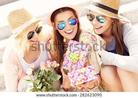 A picture of a group of friends making a surprise birthday present - stock photo