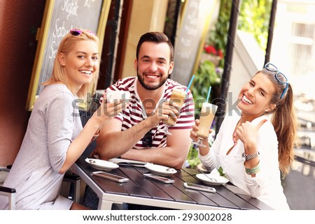 A picture of a group of friends resting in an outdoor cafe - stock photo