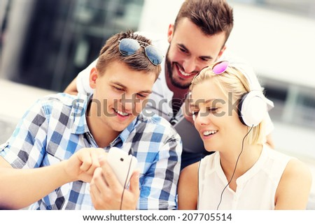 A picture of a group of friends using smartphones in the campus - stock photo