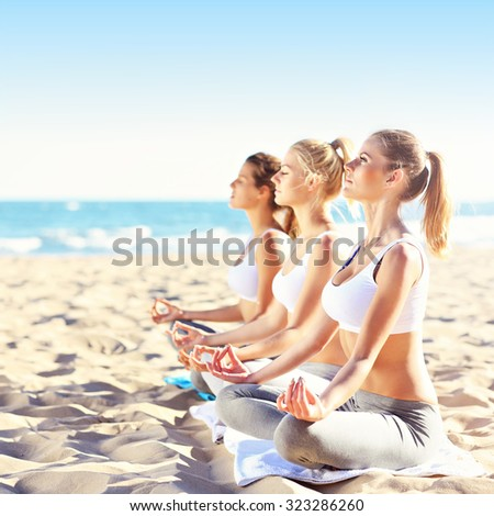 A picture of a group of women practising yoga on the beach - stock photo