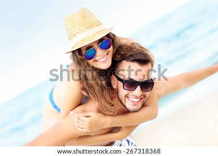 A picture of a happy couple having fun at the beach - stock photo