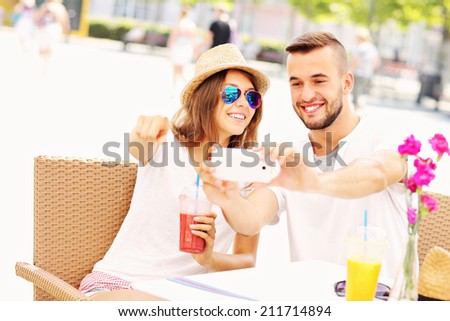 A picture of a happy couple taking pictures in a cafe