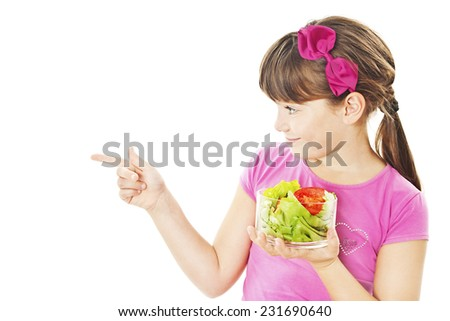 A picture of a happy little girl with vegetables pointing at something over white background  - stock photo