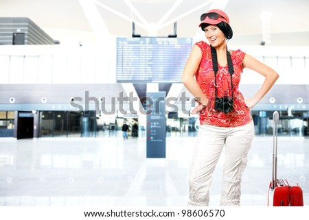 A picture of a happy woman with camera and suitcase waiting at the airport - stock photo