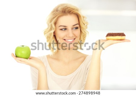 A picture of a happy woman with donut and apple in the kitchen - stock photo