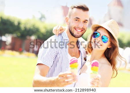 A picture of a joyful couple eating ice-cream cones in the park - stock photo