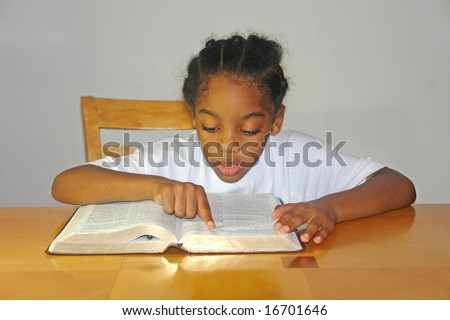 A picture of a little boy reading book at table