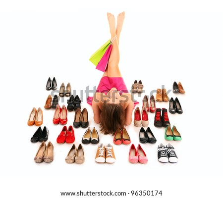 A picture of a pretty young woman lying among shoes over white background