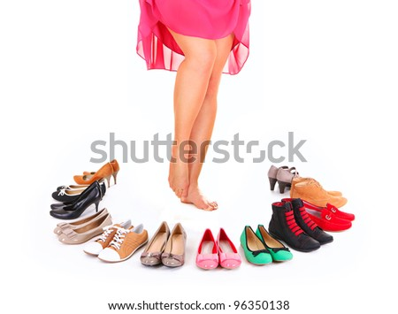 A picture of a pretty young woman sitting in the circle of shoes over white background - stock photo