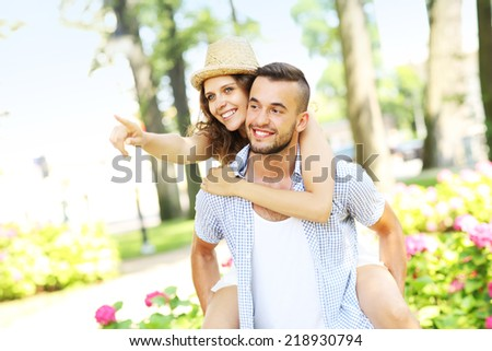 A picture of a romantic couple doing piggyback in the park