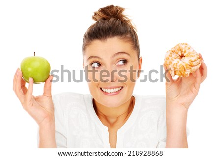 A picture of a woman choosing between apple and donut - stock photo