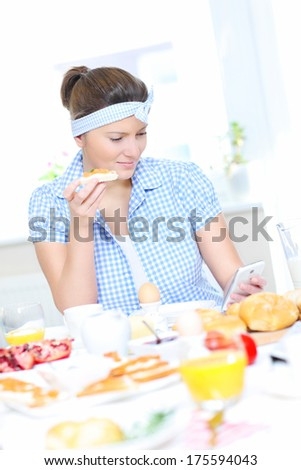 A picture of a woman eating breakfast and texting