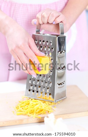 A picture of a woman grating cheese in the kitchen - stock photo