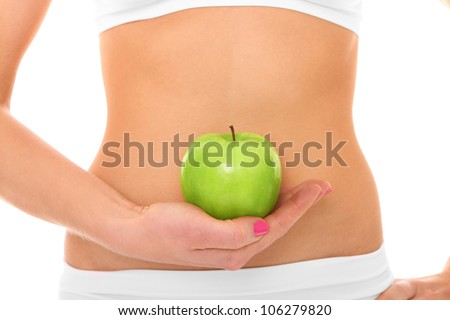 A picture of a woman holding a green apple in front of her fit belly - stock photo