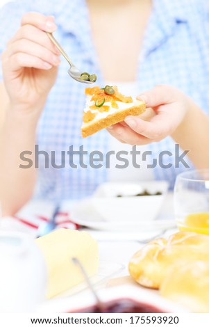 A picture of a woman preparing a salmon and capers sandwich at the table - stock photo