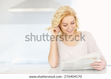 A picture of a woman reading paper at home in the morning - stock photo