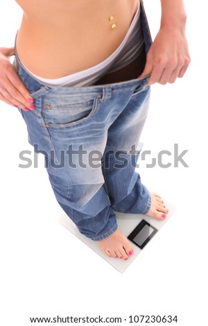 A picture of a woman standing on a bathroom scales and showing too loose jeans over white background