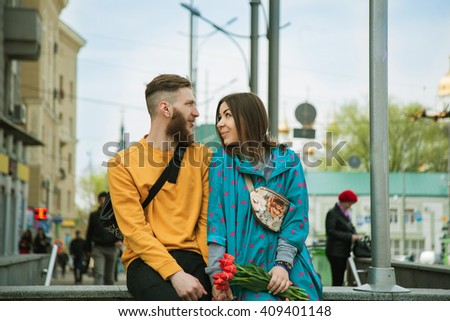 A picture of a young bright romantic couple with flowers in the gray street of city with other people. - stock photo