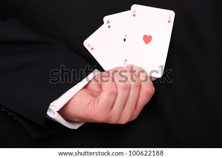 A picture of a young businessman hand holding three aces behind the back - stock photo