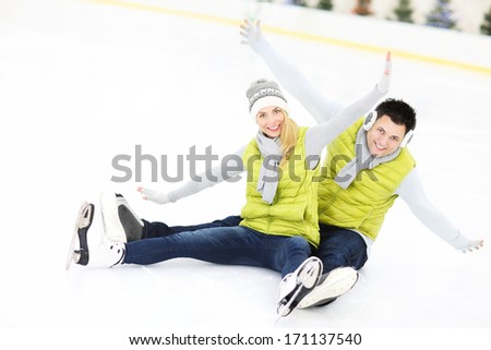 A picture of a young couple resting on an ice rink - stock photo
