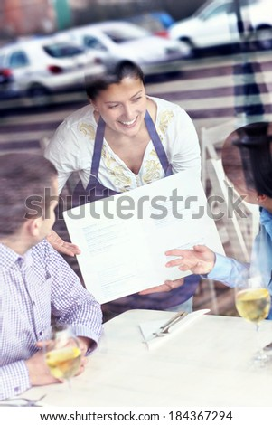 A picture of a young couple sitting in a restaurant and being served - stock photo