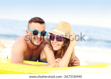 A picture of a young couple sunbathing on the beach on a sunny day - stock photo