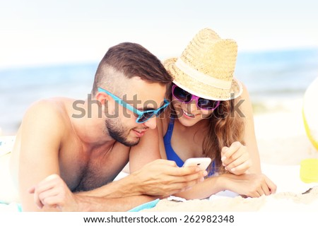 A picture of a young couple using smartphone at the beach
