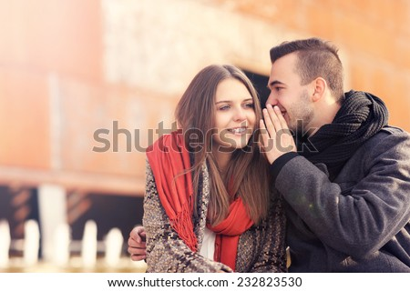 a picture of a young couple whispering on an autumn day - stock photo