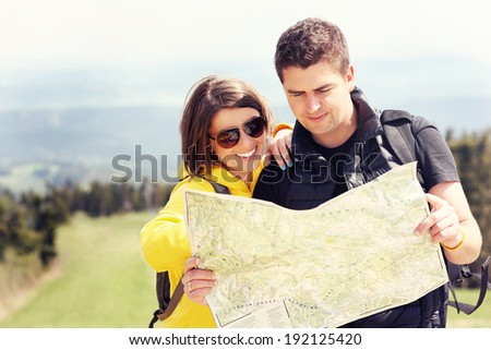 A picture of a young couple with a map in the mountains in Poland - stock photo