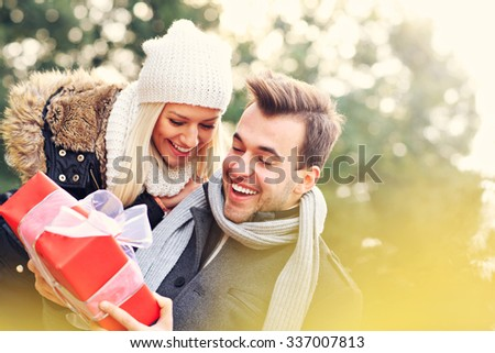 A picture of a young couple with a present in the park